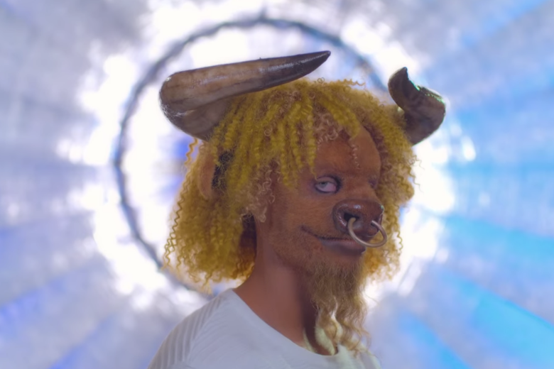 Man with yellow curly hair and a bull mask.
