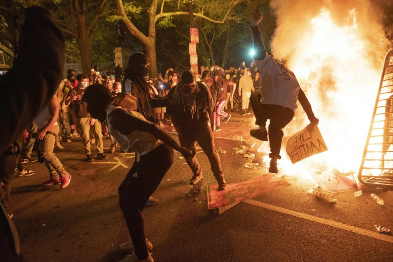 Protesters jump on a street sign near a burning barricade.