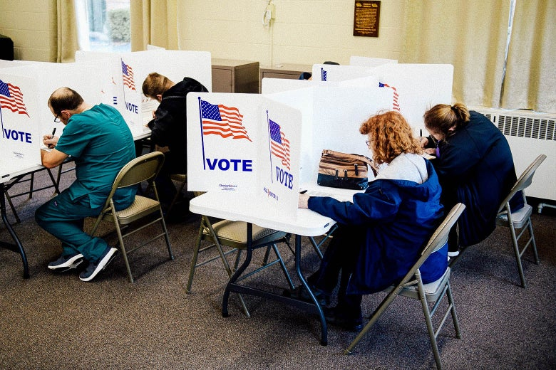 People leaning over to vote while seated at voting booths inside a church in Ohio.