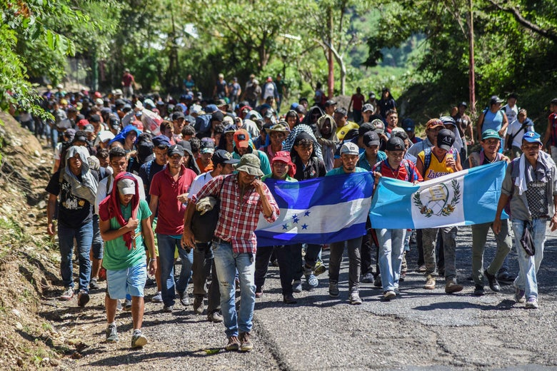 Migrants bearing Honduran and Guatemalan national flags take part in a caravan heading to the U.S.