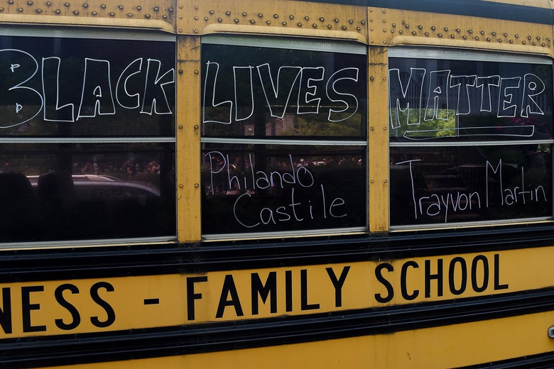 A school bus with Black Lives Matter and the names Trayvon Martin and Philando Castile written on the windows