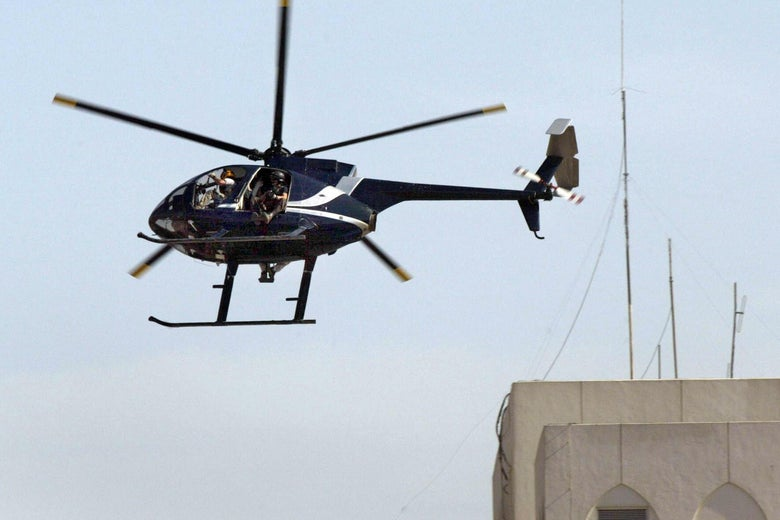 An black helicopter flies over a building.