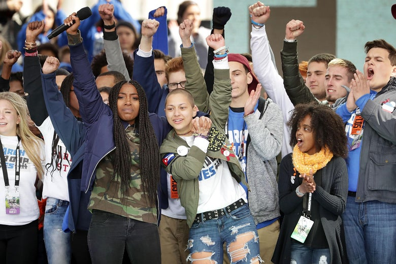 WASHINGTON, DC - MARCH 24:  Students from Marjory Stoneman Douglas High School, including Emma Gonzalez (C), stand together on stage with other young victims of gun violence at the conclusion of the March for Our Lives rally on March 24, 2018 in Washington, DC. Hundreds of thousands of demonstrators, including students, teachers and parents gathered in Washington for the anti-gun violence rally organized by survivors of the Marjory Stoneman Douglas High School shooting on February 14 that left 17 dead. More than 800 related events are taking place around the world to call for legislative action to address school safety and gun violence.  (Photo by Chip Somodevilla/Getty Images)