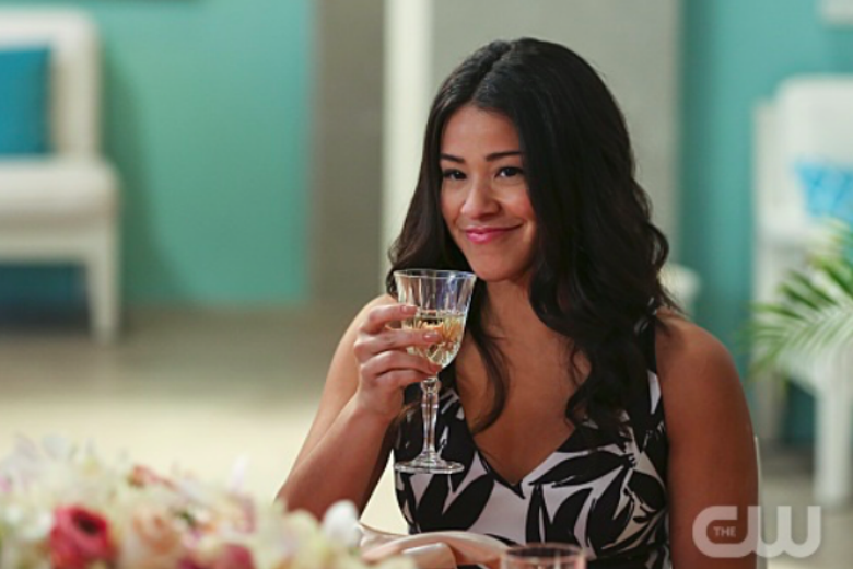 Gina Rodriguez as Jane, smiling and raising a glass.