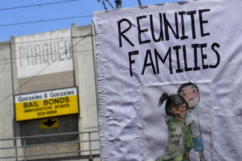 A sign during a family separation protest shows two small, terrified children hugging each other.