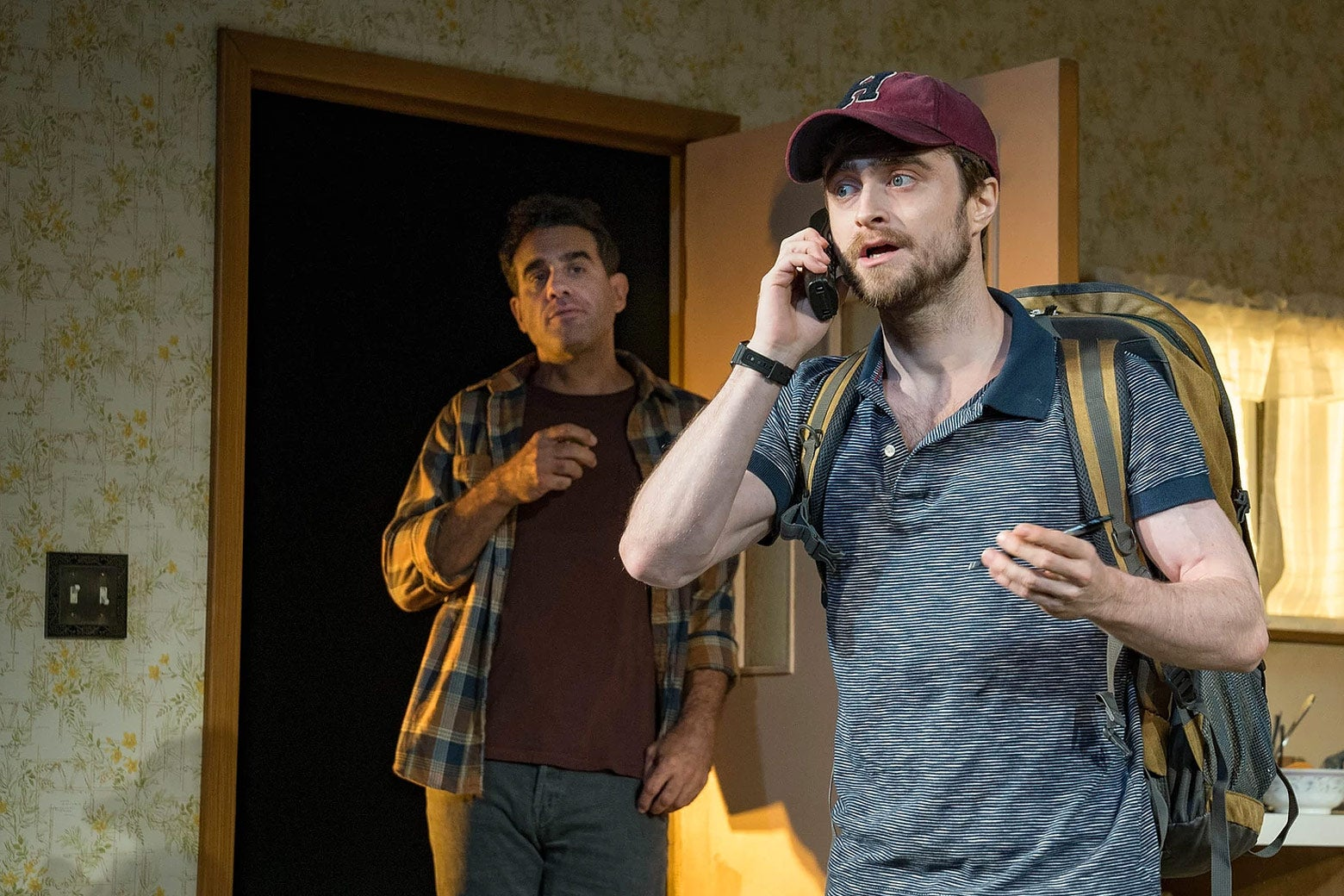 Daniel Radcliffe on the phone with a backpack on. Bobby Cannavale stands in the doorway.