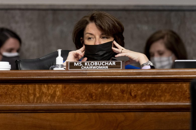 Amy Klobuchar holds her mask in place while sitting behind the dais.