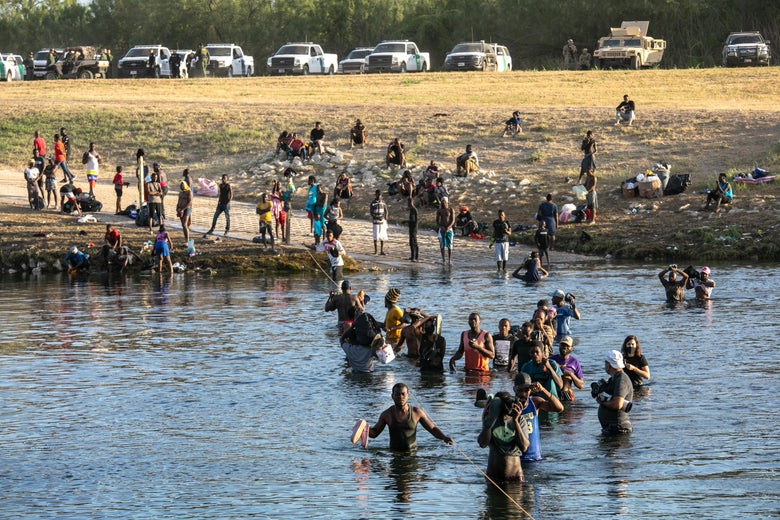 Haitian migrants standing in front of a body of water while others wade through it