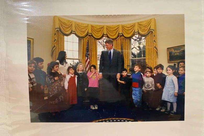 A picture of a page in a family photo album that contains a photo of a bunch of children in the Oval Office with Bill Clinton in 1993.