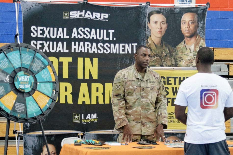 "Man in army fatigues standing behind a table talking to another man in a tee shirt, in front of a poster reading ""Sexual Harassment, Sexual Assault: Not in Our Army""."