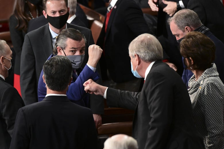Ted Cruz in Congress wearing a mask and holding his fist out to a colleague.