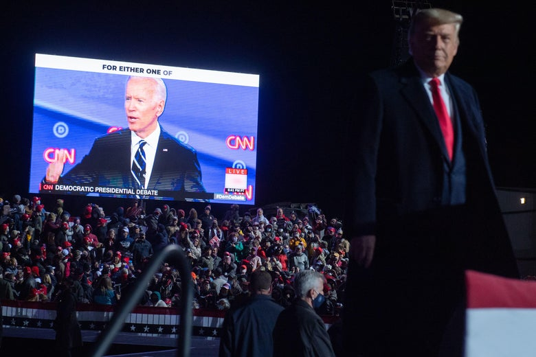 Joe Biden is on a giant screen that's playing to a packed crowd. Donald Trump is in the foreground.