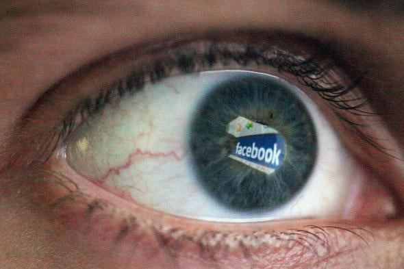 An eyeball with the Facebook logo reflected in it.