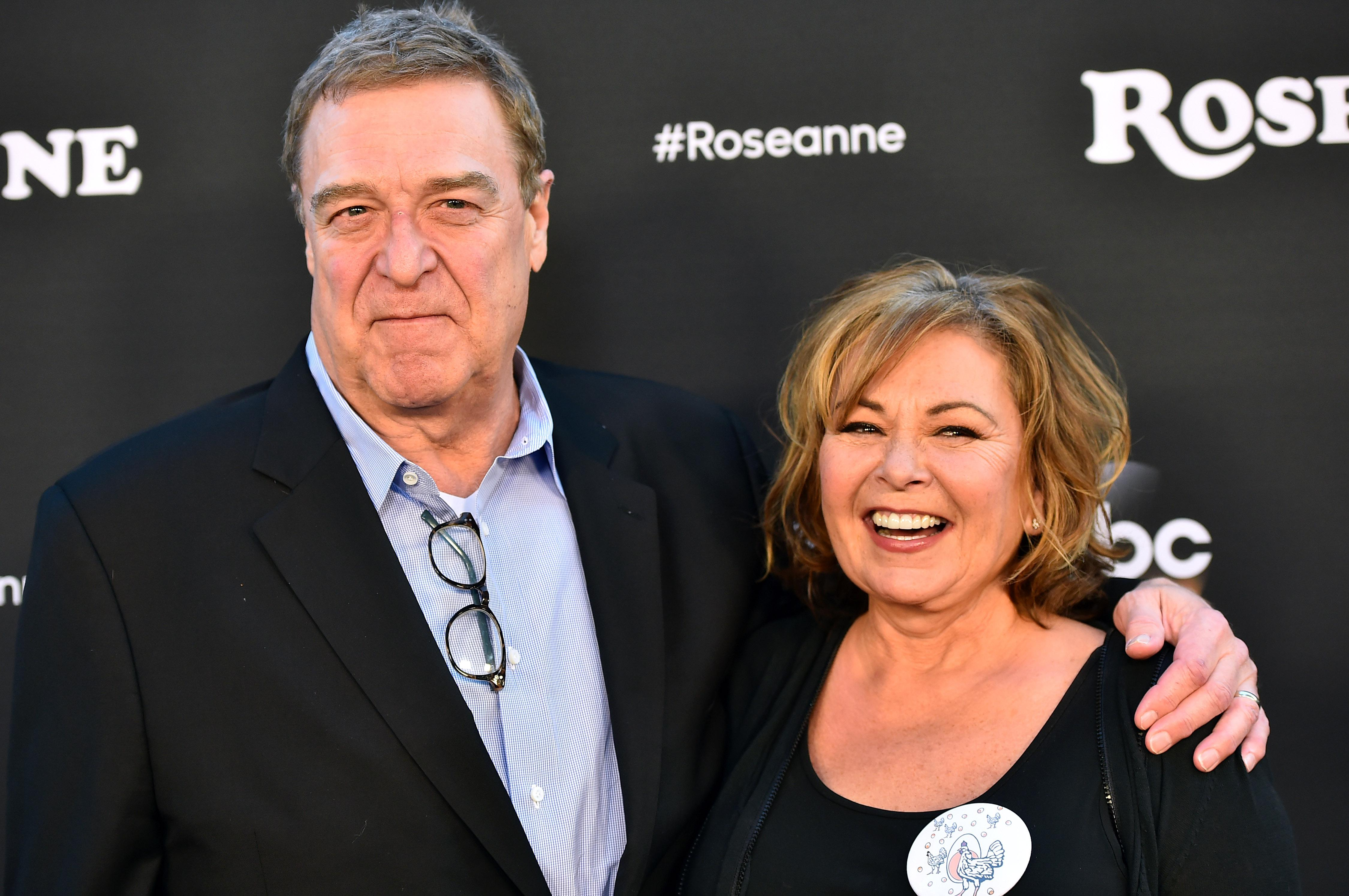 John Goodman and Roseanne Barr in front of a black background with #Roseanne printed on it.