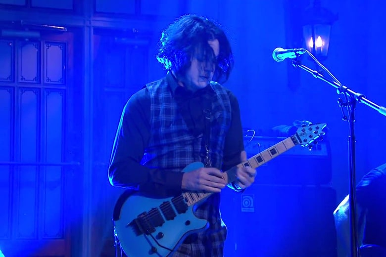Musician Jack White, tapping on the fretboard of a blue Eddie Van Halen guitar. White is wearing a plaid vest and lit by blue light.