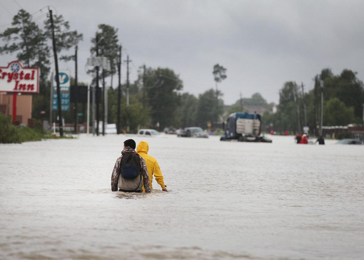 People make their way out of a flooded neighborhood