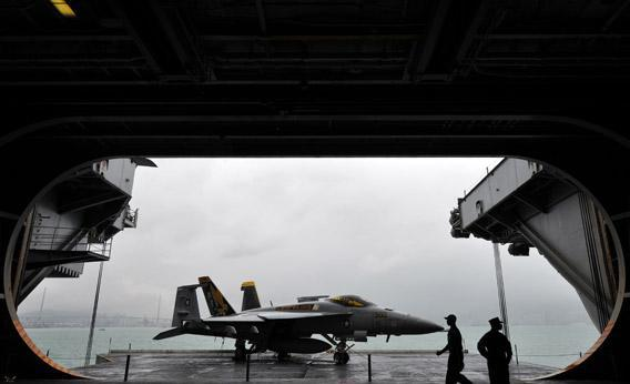 US navy servicemen are seen with an F/A-18 Hornet warplane on the USS George Washington, a nuclear powered aircraft carrier, in Hong Kong on November 9, 2011.