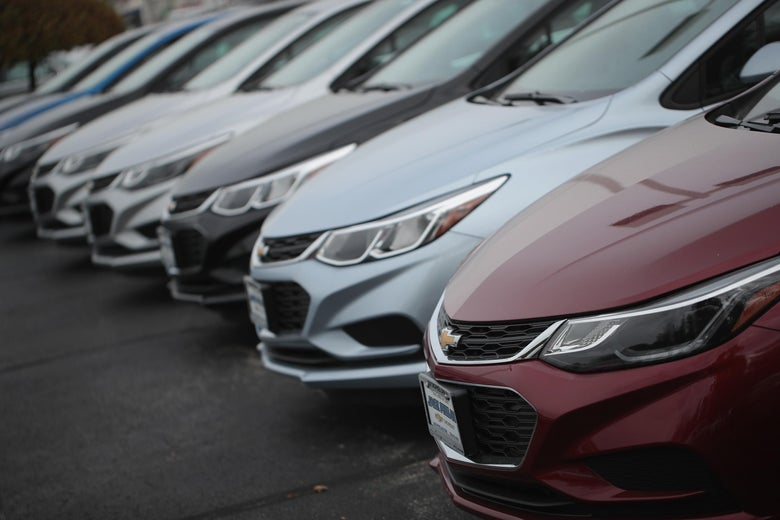 A line of several Chevy Cruzes of various colors viewed from the side