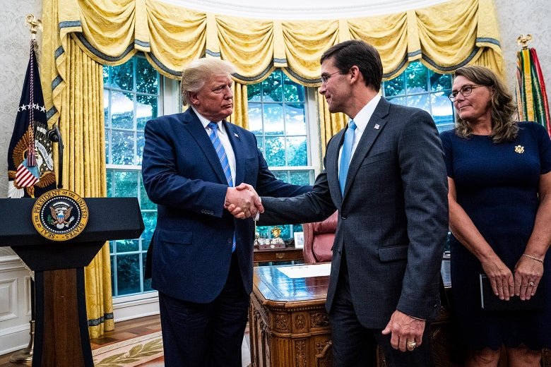 Mark Esper shakes hands with the president as his wife, Leah Esper, looks on.