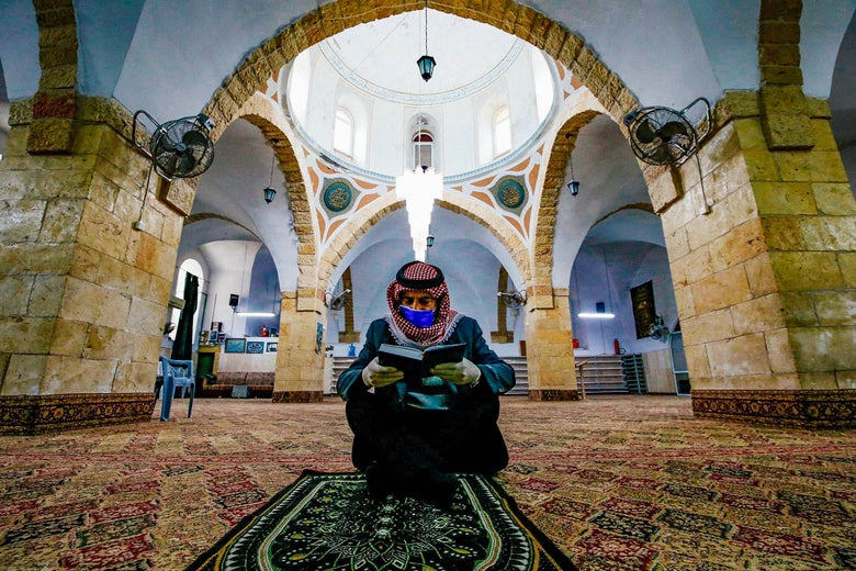 A Muslim man wearing gloves and a face mask sits on the floor reading the Quran alone.