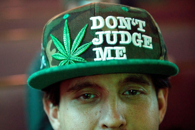 """A man wears a baseball cap that says, """"Don't judge me,"""" and features a marijuana leaf."""