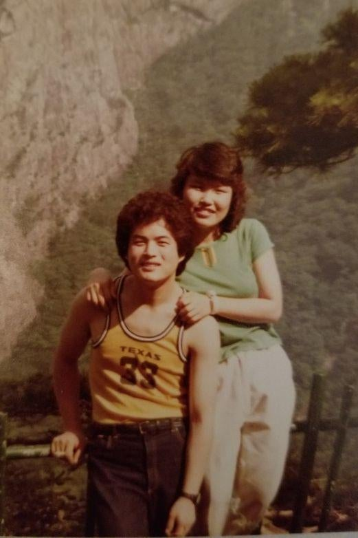In a faded photograph, woman puts her arms on the shoulders of a man in a basketball jersey.
