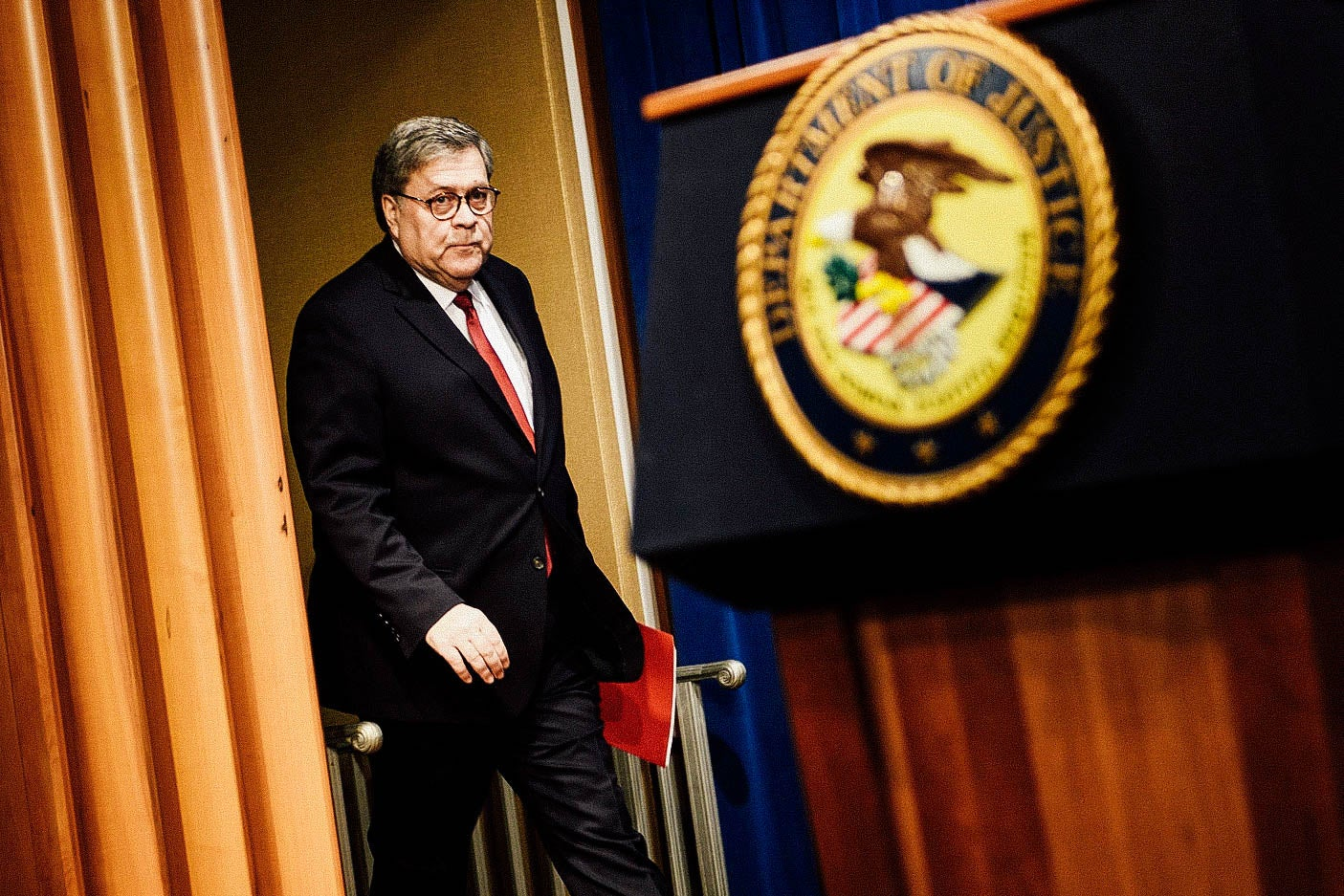 William Barr walks toward a DOJ podium