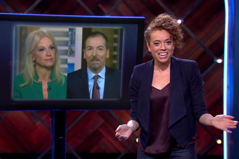 Michelle Wolf stands in front of a picture of Kellyanne Conway and Chuck Todd.