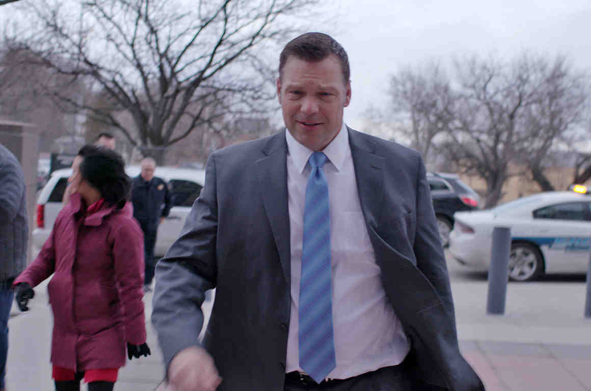 Kansas Secretary of State Kris Kobach walks into a courtroom.