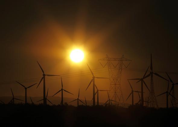 The sun rises behind windmills at a wind farm, February 9, 2011.