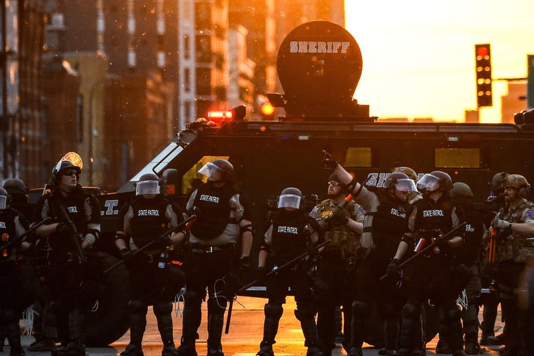Officers with riot gear on stand in front of an armored vehicle at sunset.