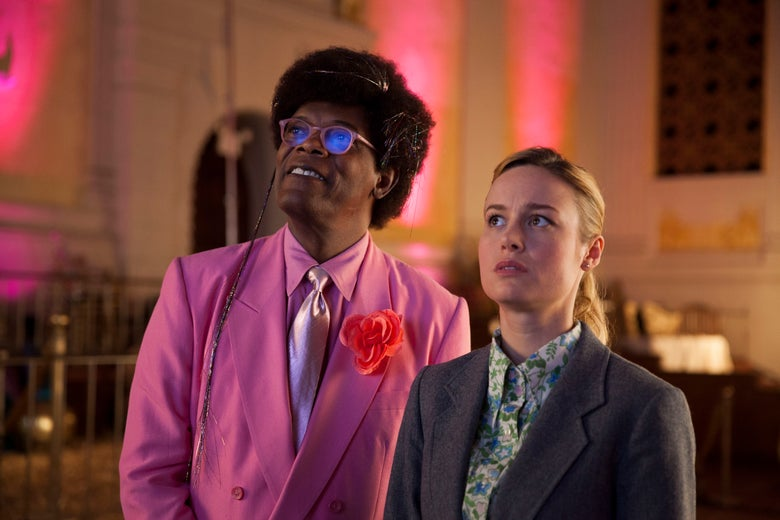 Samuel L Jackson in a pink suit and Brie Larson in a flowered shirt stare off into the distance.