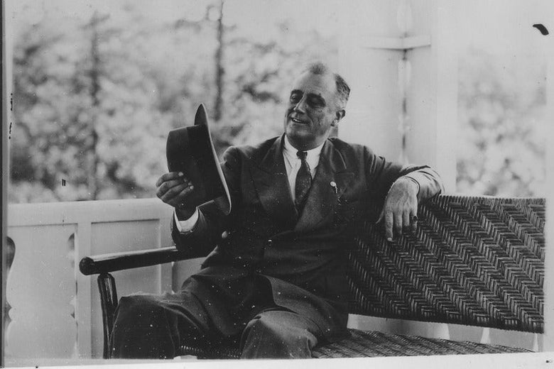 FDR seated on a sofa, looking at the hat he's holding in his right hand and smiling