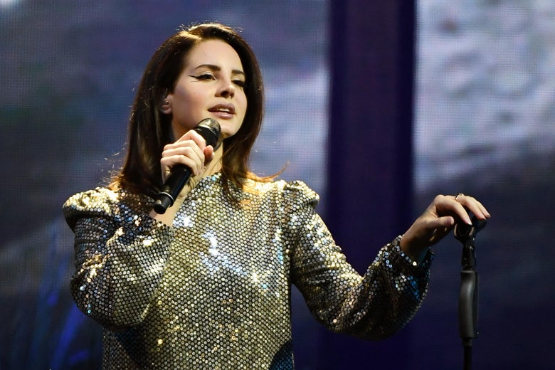 Lana Del Rey holds a microphone.