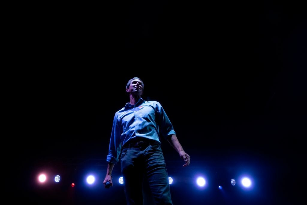 Beto O'Rourke, shot from below in hero/rock-star fashion with stage lights in the background.