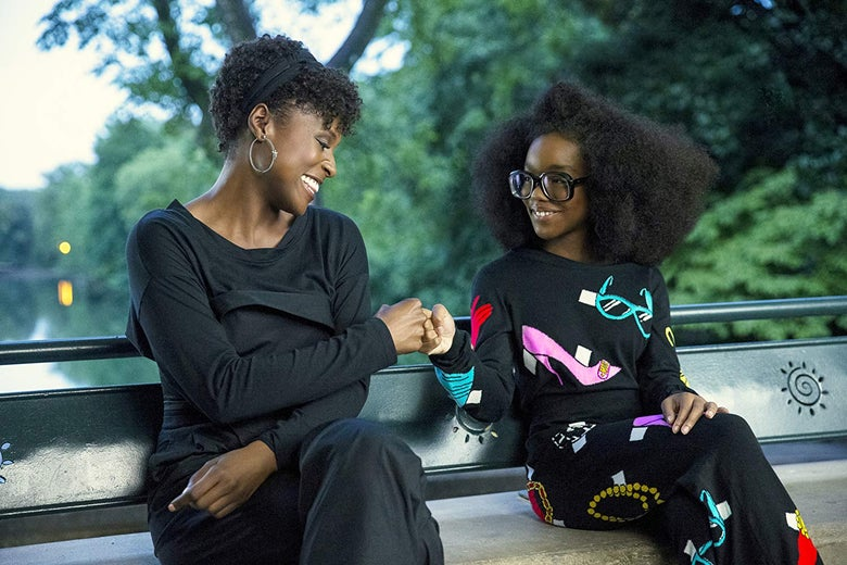 Issa Rae and Marsai Martin fist-bump while sitting on a bench.