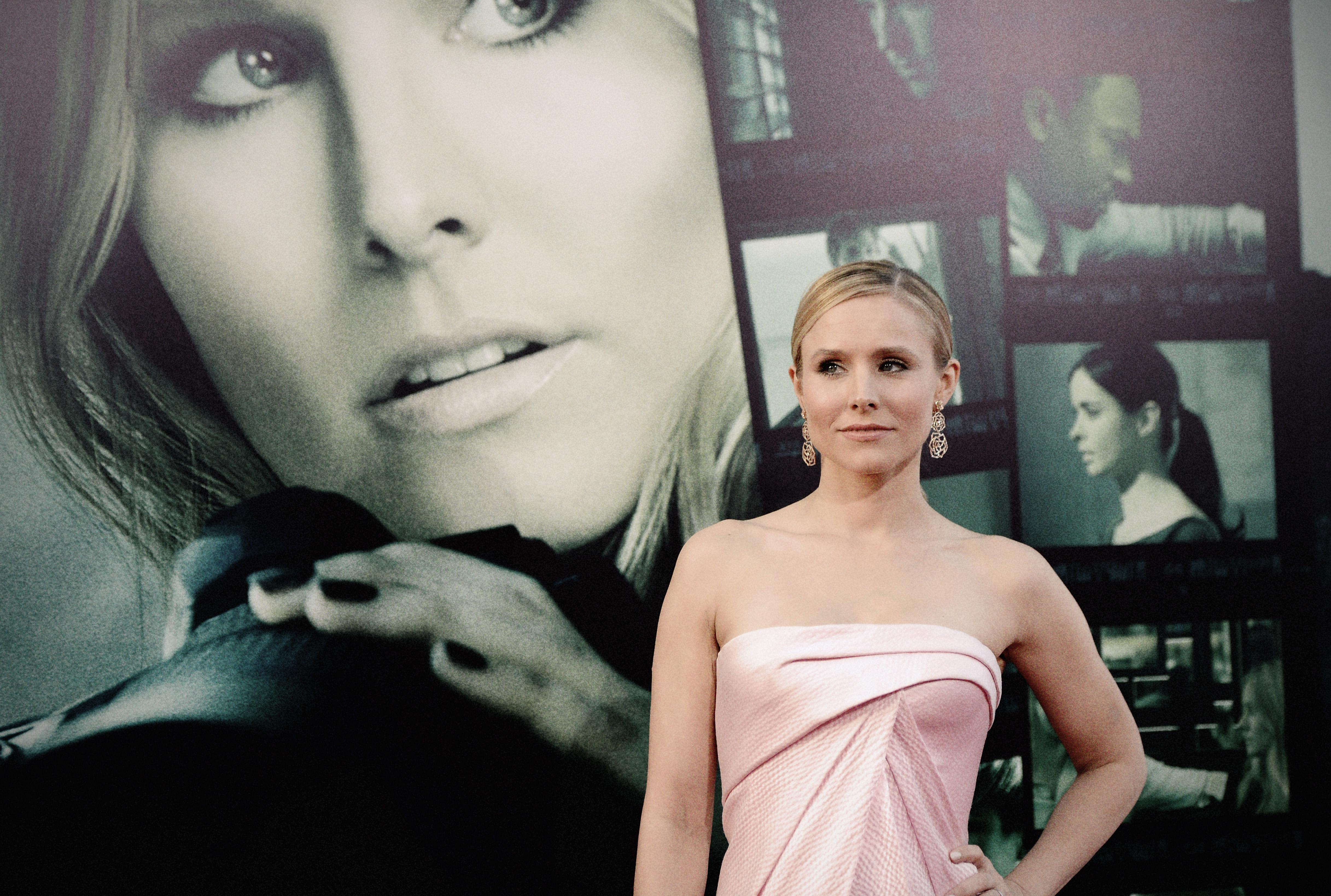 Kristen Bell wears a sleeves pink dress and stands in front of an enormous Veronica Mars poster on the red carpet.