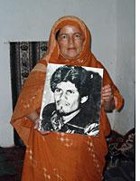 Sahrawi woman holding a picture of El Ouali, the founder of the Polisario Front. Click image to expand.