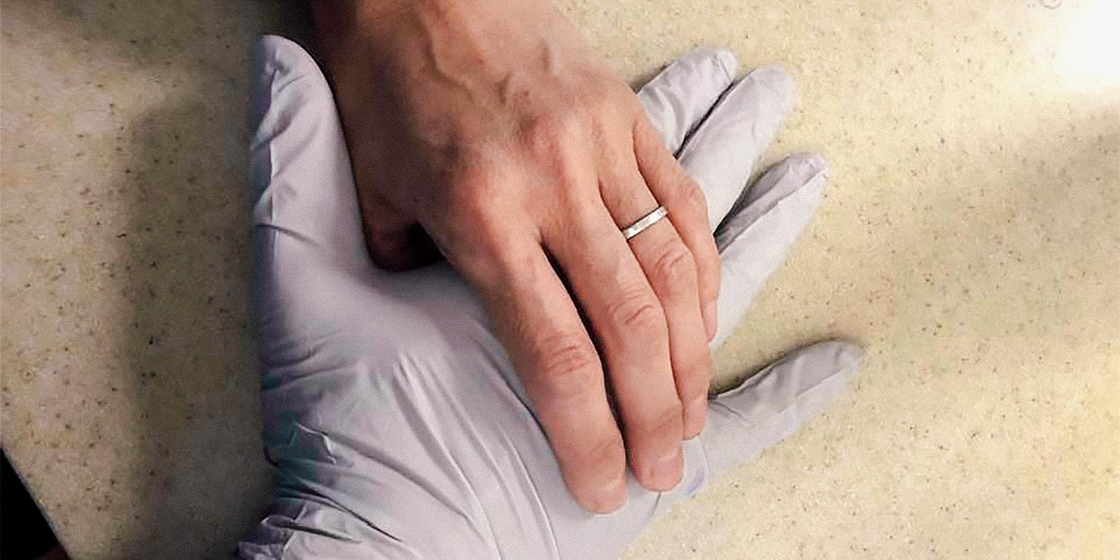 Hanna's bare hand with a wedding ring holding Steve's hand in a surgical glove
