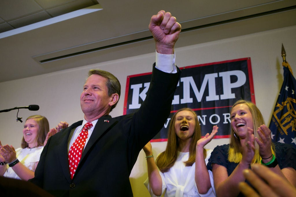 Brian Kemp raises his hand in triumph from behind a lectern at his primary victory party, which appears to be taking place in an office park conference room.