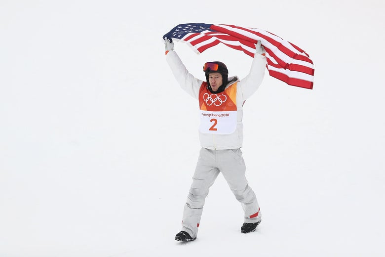 Shaun White holds an American flag over his head in celebration.