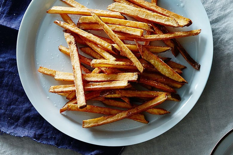 Crispy-looking french fries on a white plate set against a blue linen tablecloth.
