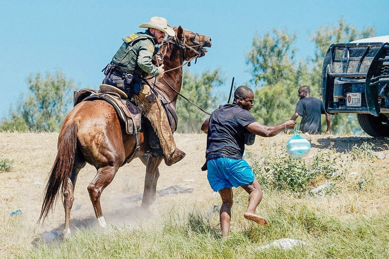 A border patrol agent on horseback chasing and using his reins to try to stop a Haitian migrant, who appears to be running.