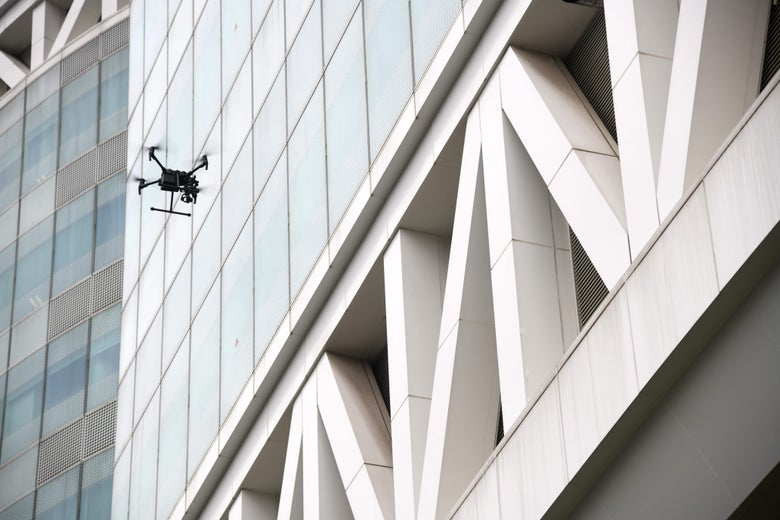 A small drone flies in front of windows on a large building.
