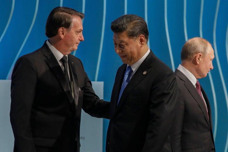Bolsonaro speaks with Xi. Putin is seen behind them.