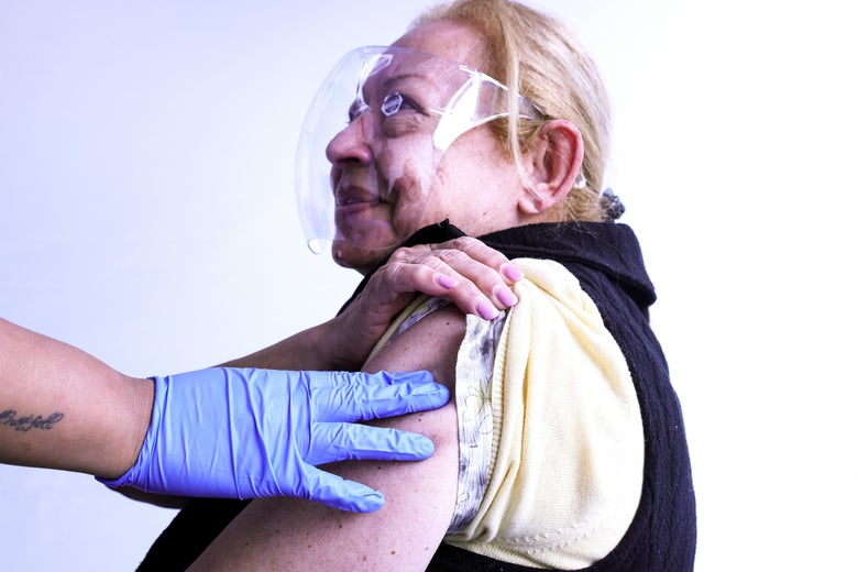 A woman in a clear face shield smiles at a health worker after receiving her vaccine.