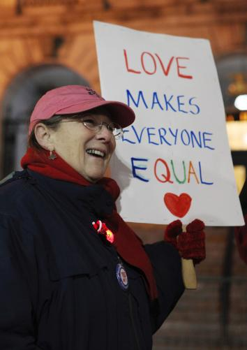 Gail Berenson greets couples gathering to receive marriage licenses at the City Hall in Portland, Maine, as same-sex couples gained the right to marry in that state in December 2012.