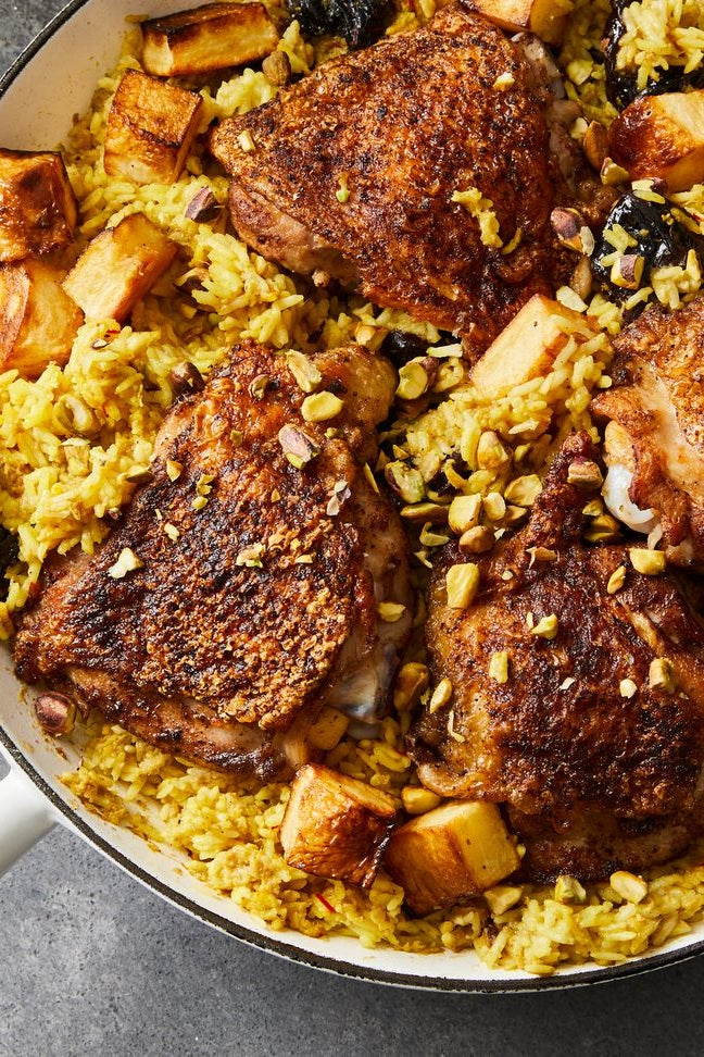 Garam masala chicken thighs with cubed potatoes and saffron rice in a skillet