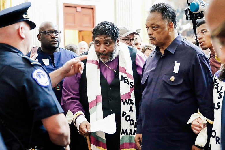 "Police stop the Rev. William Barber, the Rev. Jesse Jackson, and other clergy and demonstrators attempting to deliver a letter to the Senate on May 21 at the U.S. Capitol in Washington. Barber is wearing a scarf with the words ""Jesus Was a Poor Man"" visible."