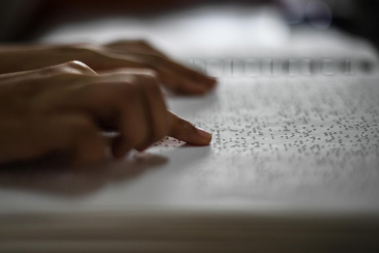 A visually impaired person reads a page in Braille.